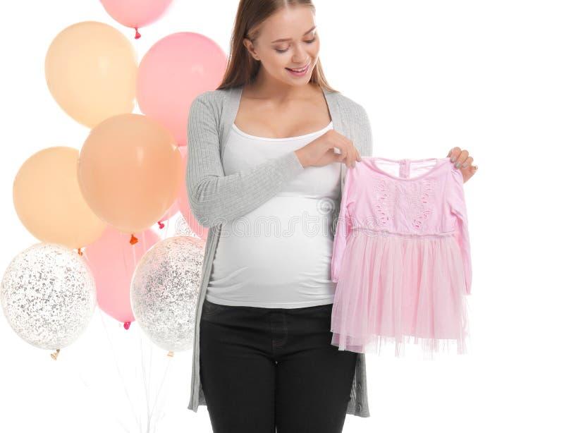 Schöne schwangere Frau mit Babykleider- und -luftballonen auf weißem Hintergrund lizenzfreie stockfotos