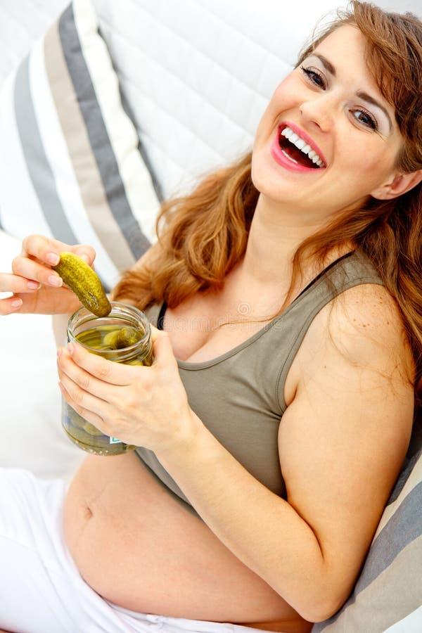 Schöne schwangere Frau mit Glas Essiggurken lizenzfreie stockbilder