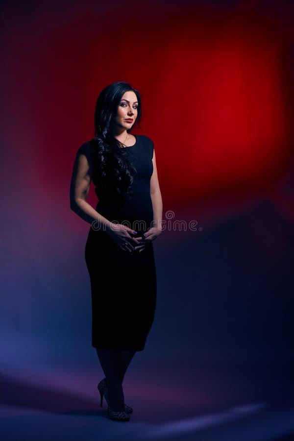 Schöne schwangere Frau mit hellem Make-up, langes schwarzes Haar, in einem Schwarzinstallationskleid, das in einem Fotostudio auf lizenzfreies stockfoto