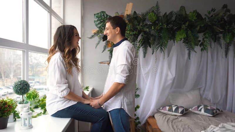 Schöne schwangere Frau und ihr hübscher Ehemann, die ihre Bäuche umarmt stockfoto