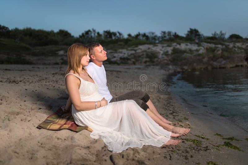 Schöne schwangere Frau und ihr Mann, die auf der Küste sitzt stockbild