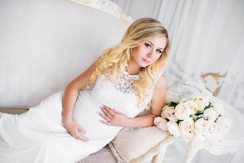 Schöne schwangere Frau, wenn auf das Baby gewartet wird Schwangerschaft Sorgfalt, Weichheit, Mutterschaft, Geburt lizenzfreies stockfoto