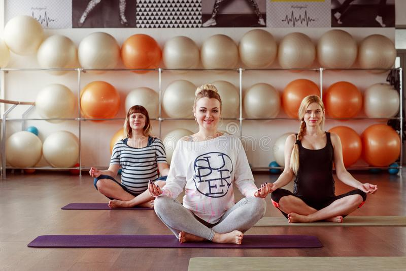 Schöne schwangere Frauen im Yoga klassifizieren Sitzplätze in einem Eignungsbolzen lizenzfreie stockfotografie