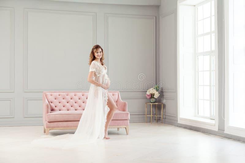 Schöne schwangere junge Frau im weißen Kleid-peignoir, das nahe dem rosa Sofa, mit Liebe ihren Bauch halten steht lizenzfreie stockbilder