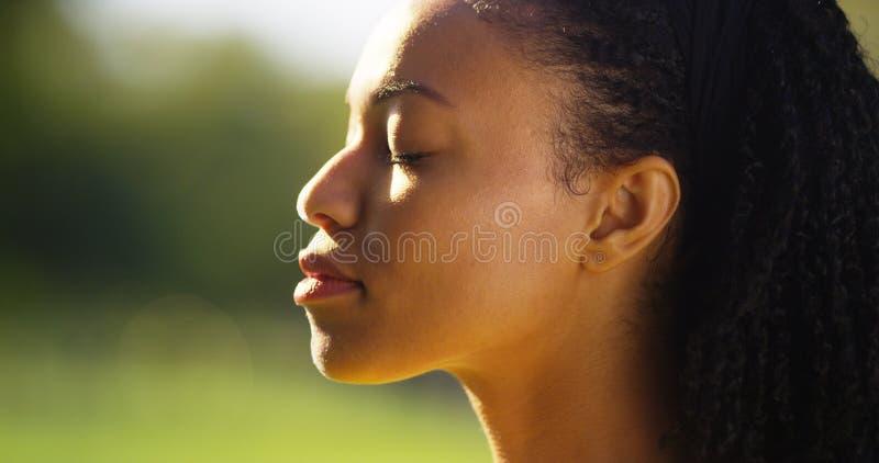 Schöne schwarze Frau, die der Sonne auf ihrem Gesicht glaubt stockfoto
