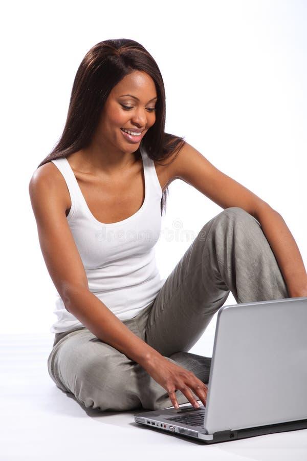 Schöne schwarze Frau, die großes Lächeln des Laptops verwendet stockfoto