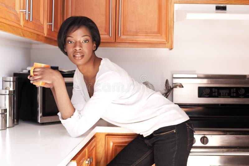 Schöne schwarze Frauen im Küchelächeln stockfotos