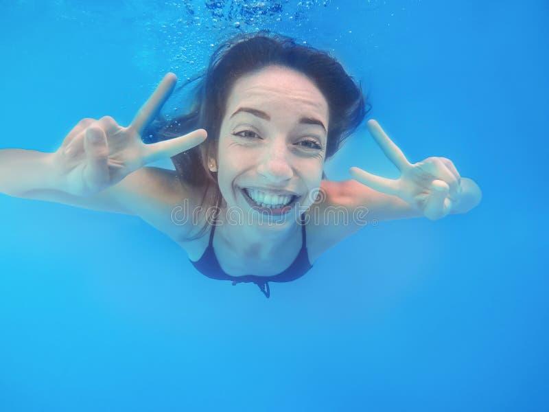 Schöne Schwimmen der jungen Frau im Pool lizenzfreies stockbild