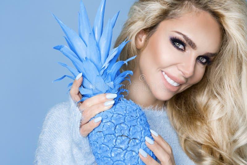 Schöne, sexy Blondine des Porträts in der blauen Strickjacke, stehend auf einem blauen Hintergrund und halten eine blaue Ananas lizenzfreie stockfotos
