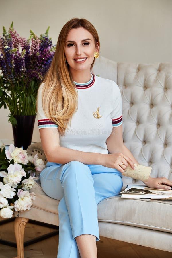 Schöne sexy Blondine sitzen auf dem Sofa im Toilettenklo lizenzfreies stockfoto