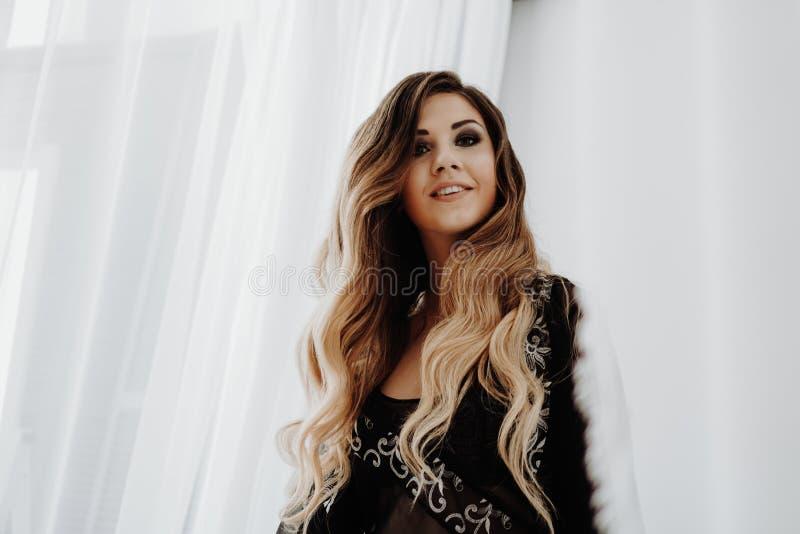 Schöne sexy braune gelockte lange Haarfrau, die im Bett aufwirft lizenzfreie stockfotografie