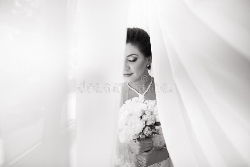 Schöne sexy Braut im weißen Kleid, das unter Vorhang aufwirft stockfoto