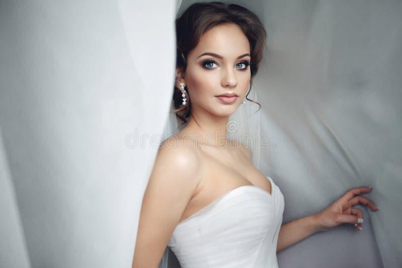 Schöne sexy Braut im weißen Kleid, das unter Vorhang aufwirft stockbilder