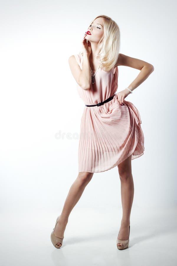 Schöne sexy elegante auffallende Blondine mit hellem Make-up im rosa Kleid mit dlinnymi schlanken Beinen im Studio auf Weiß stockfoto