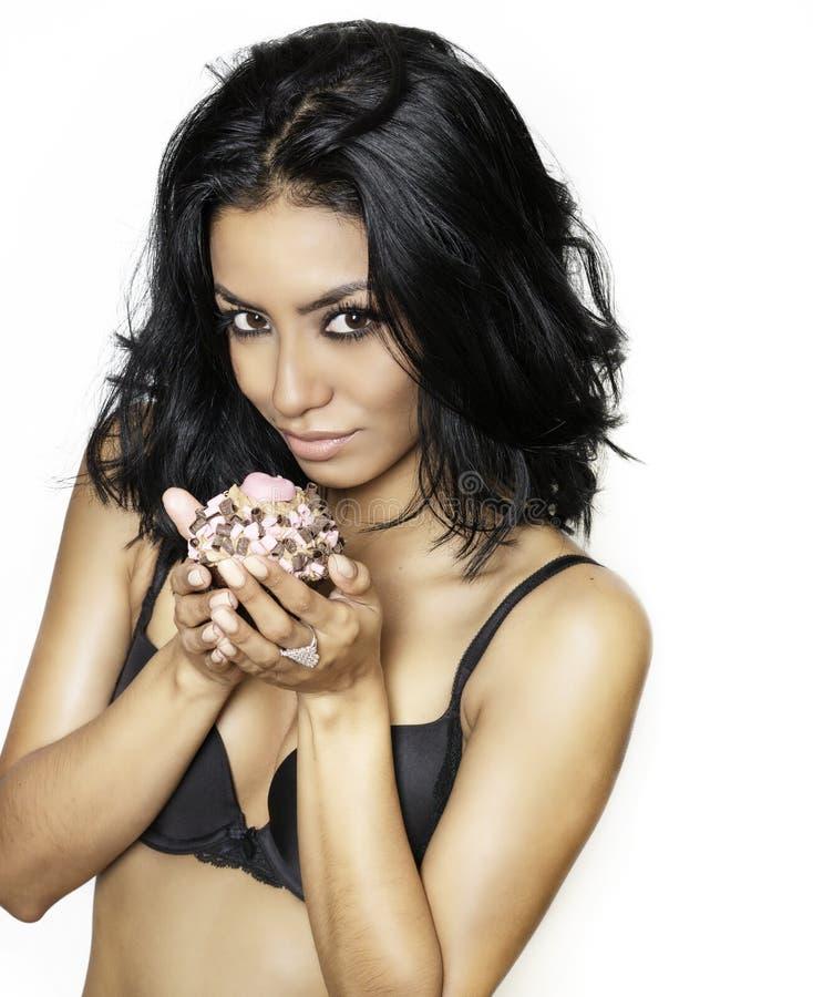 Schöne sexy exotische junge Frau, die kleinen Kuchen hält stockfoto
