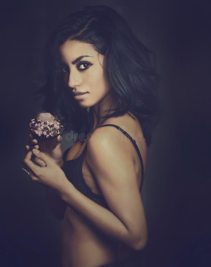 Schöne sexy exotische junge Frau, die kleinen Kuchen hält lizenzfreie stockfotografie