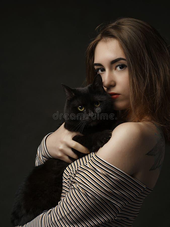Schöne sexy Frau in der schwarzen haltenen schwarzen Katze Schöne junge und stilvolle Frau, die eine graue Katze hält Abschluss o stockbilder