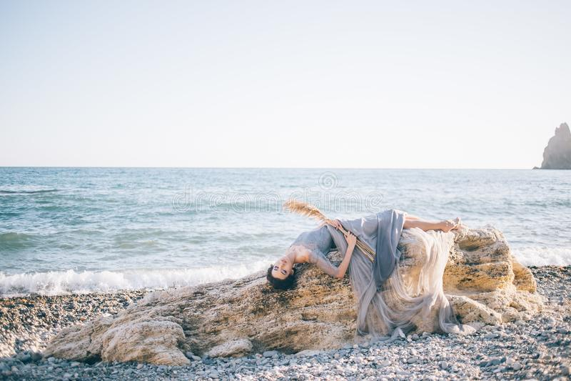 Schöne sexy Frau in einem langen Kleid von voila liegt auf einem großen Stein nahe dem Meer stockfoto