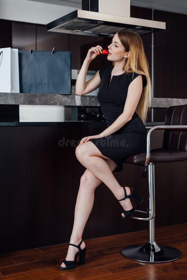 Schöne sexy Frau in einer kleinen Schwarze, die nach der Einkaufsc$essenerdbeere zu Hause sitzt auf Barhocker sich entspannt stockfoto