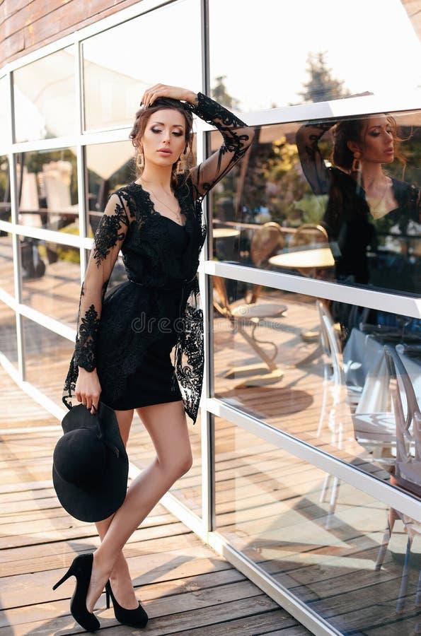 Schöne sexy Frau mit dem dunklen Haar im eleganten schwarzen Kleid und im Hut lizenzfreie stockfotos