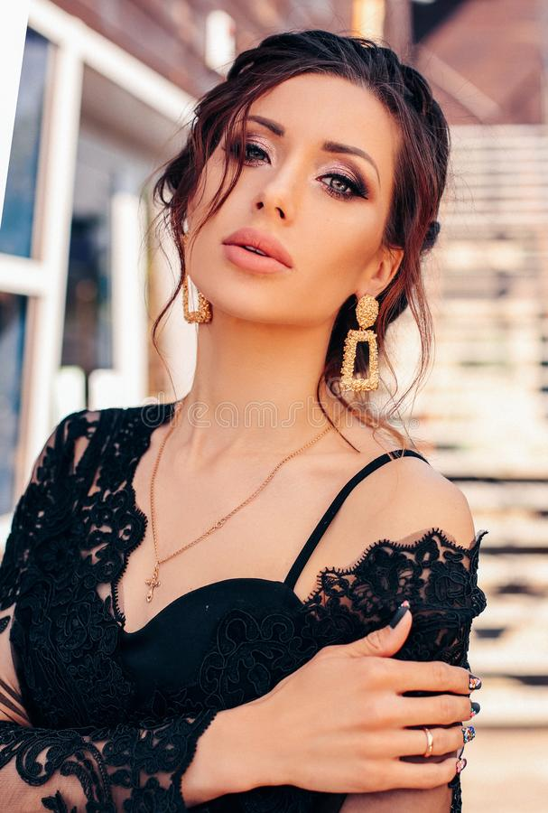 Schöne sexy Frau mit dem dunklen Haar im eleganten schwarzen Kleid und im Hut stockfotografie