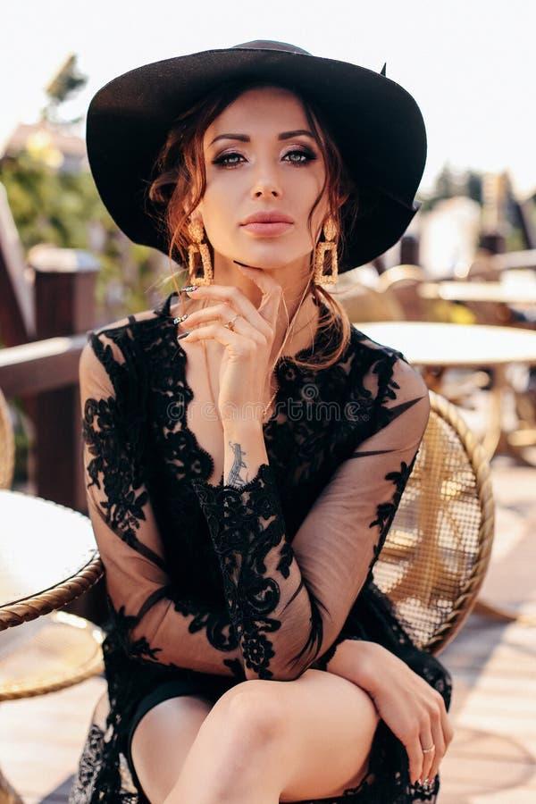 Schöne sexy Frau mit dem dunklen Haar im eleganten schwarzen Kleid und im Hut lizenzfreies stockbild
