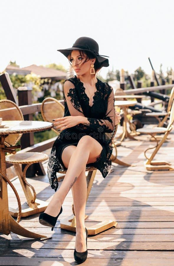Schöne sexy Frau mit dem dunklen Haar im eleganten schwarzen Kleid und im Hut stockfoto