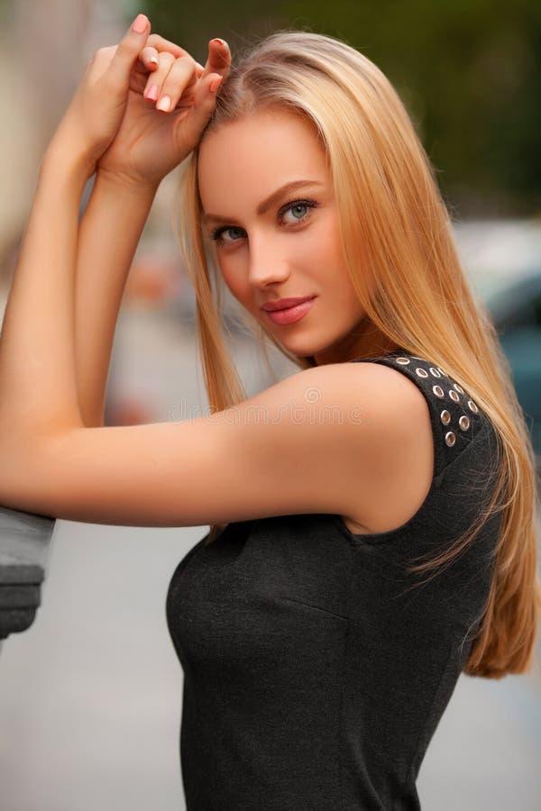 Schöne sexy Frau mit der schwarzes Kleider- und des blonden Haaresaufstellung im Freien Art- und Weisemädchen-Portrait lizenzfreie stockbilder