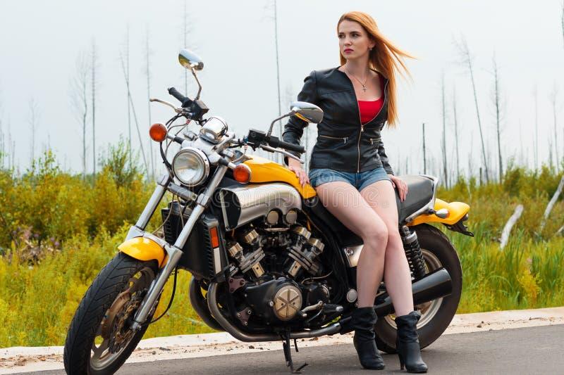 Schöne sexy Frau mit Motorrad auf der Straße lizenzfreie stockfotografie