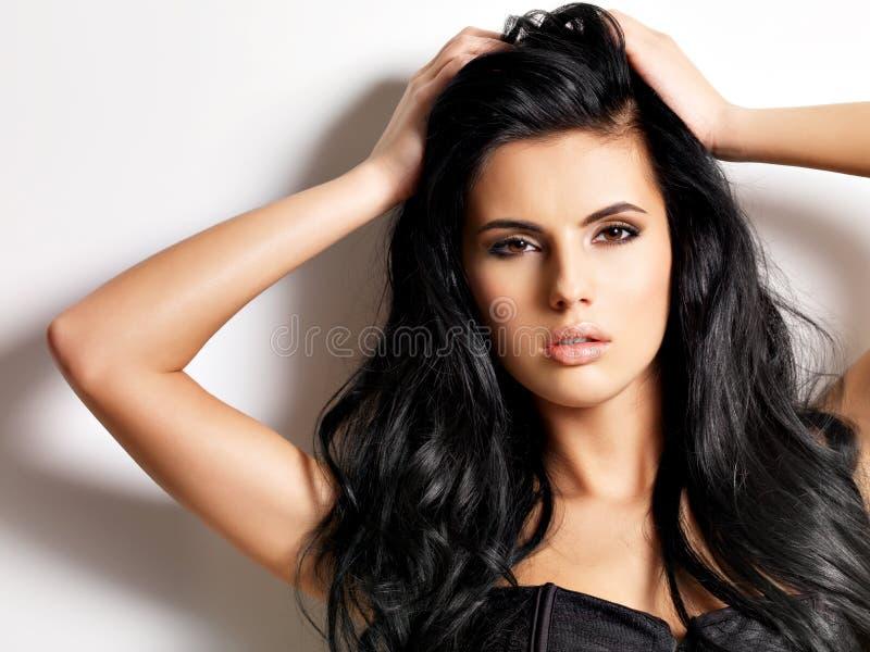 Schöne sexy junge Brunettefrau mit dem langen Haar stockbild