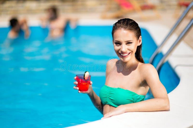 Schöne sexy junge Frau im Pool während des Sommers lizenzfreie stockfotos