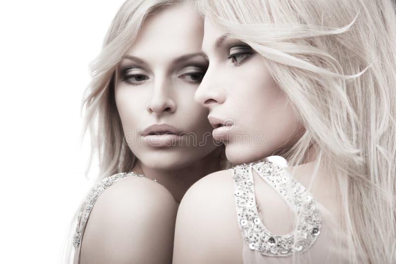 Schöne sexy junge Frau nahe Spiegel über Weiß lizenzfreie stockfotos