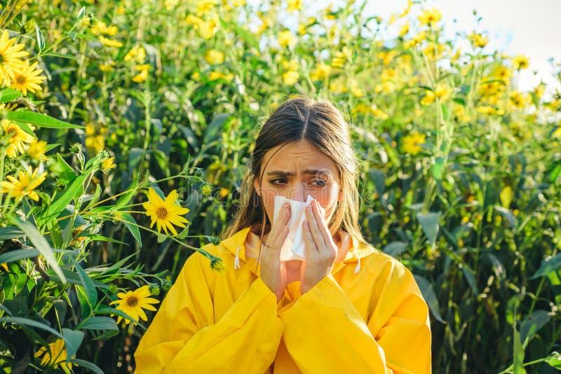 Schöne sexy Lügen der jungen Frau auf Blumenhintergrund Junges Mädchen, das Papiergewebe in einer Hand niest und hält und lizenzfreie stockfotos