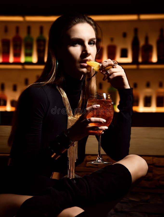 Schöne sexy Mode Brunettefrau in Barrestaurant Entspannungstrinkendem orange aperol sprit Cocktail lizenzfreie stockfotografie