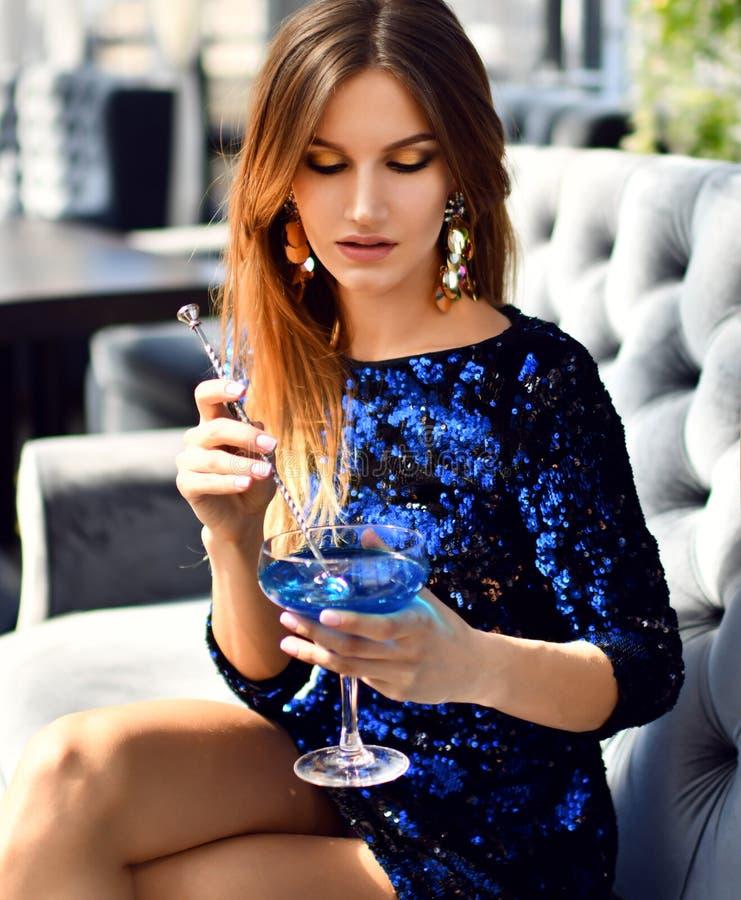 Schöne sexy Mode Brunettefrau in teures Innenrestaurant trinkendem trinkendem blauem Margaritacocktail auf Sonnenuntergang stockfotos