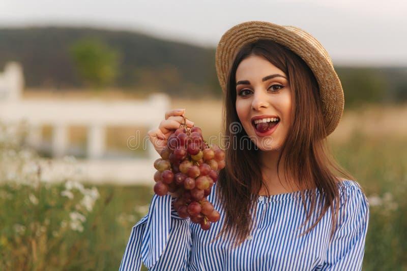 Schöne Show der schwangeren Frau und rote Trauben essen Gesunde Nahrung Frische Früchte Glückliches Frauenlächeln stockfotos