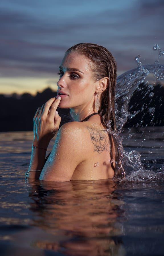 Schöne sinnliche Frau allein im UnendlichkeitsSwimmingpool lizenzfreie stockbilder