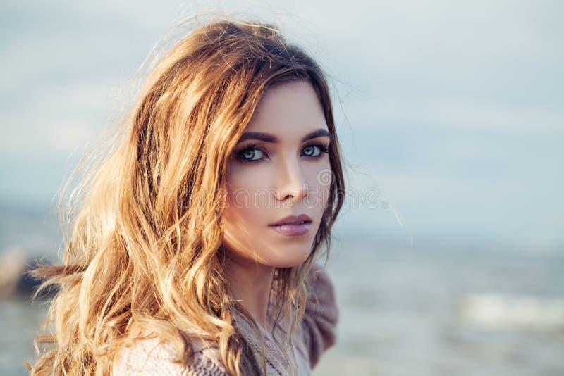Schöne sinnliche Frau mit dem langen gelockten Haar am sonnigen Tag lizenzfreie stockbilder