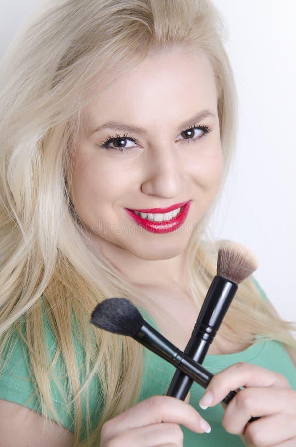 Schöne sinnliche junge blonde haltene Make-upbürsten gekreuzt lizenzfreie stockbilder