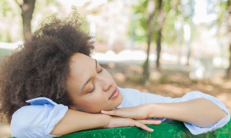 Schöne sinnliche schwarze Frau, die in der Natur träumt stockfotografie