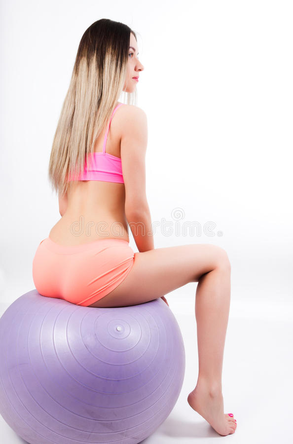 Schöne Sitzfrau, die Übungen auf dem Sport tut stockfoto
