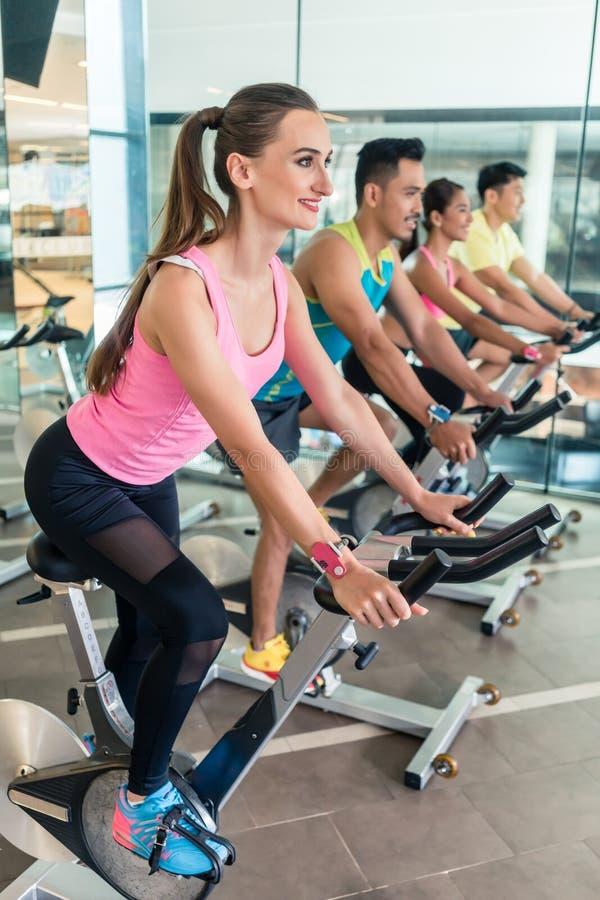 Schöne Sitzfrau, die während des Herz Trainings an Innenradfahrencla lächelt lizenzfreie stockbilder