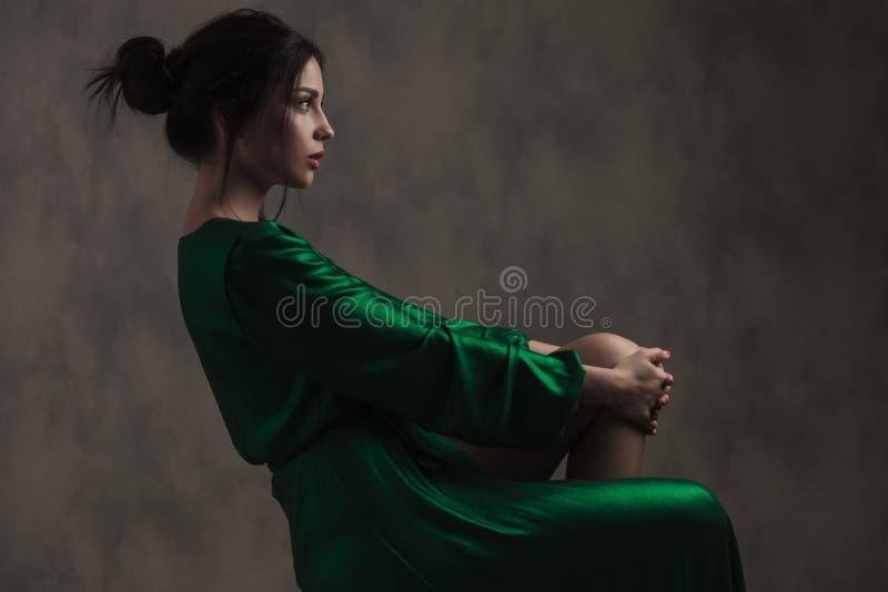Schöne Sitzfrau im grünen Kleid, das ihr Bein hält stockbild