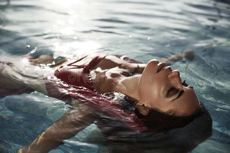 Schöne sonnen-gebräunte Frau mit geschlossenen Augen im Wasser genießt ihre Ferien, indem sie nimmt, ein Sonnenbad nimmt in der S stockfotografie