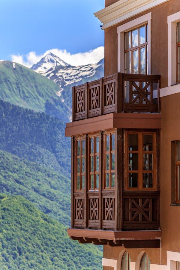 Schöne sonnige Landschaft des Hotelgebäudes am Sichi-Gebirgsskiort auf grünem Wald, schneebedeckte Bergspitzen lizenzfreies stockbild