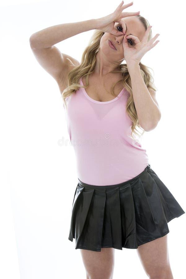 Schöne spielerische junge kaukasische Frau, die durch ihren Fing schaut lizenzfreies stockbild