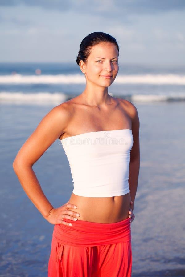 Schöne Sportfrau, die durch die Küste sich entspannt stockfoto