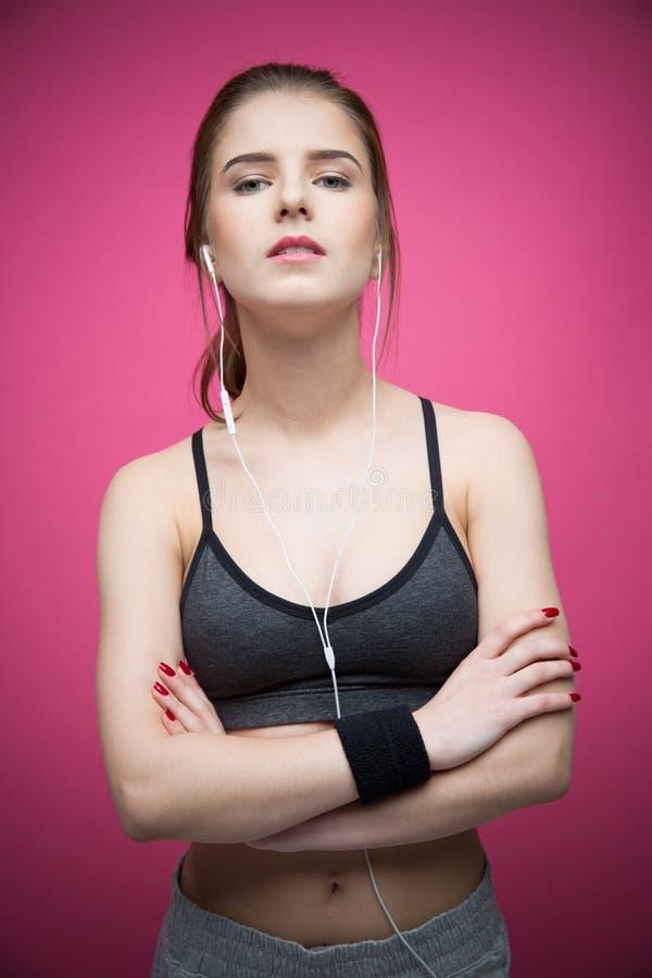 Schöne Sportfrau, die mit den Armen gefaltet steht stockfotografie