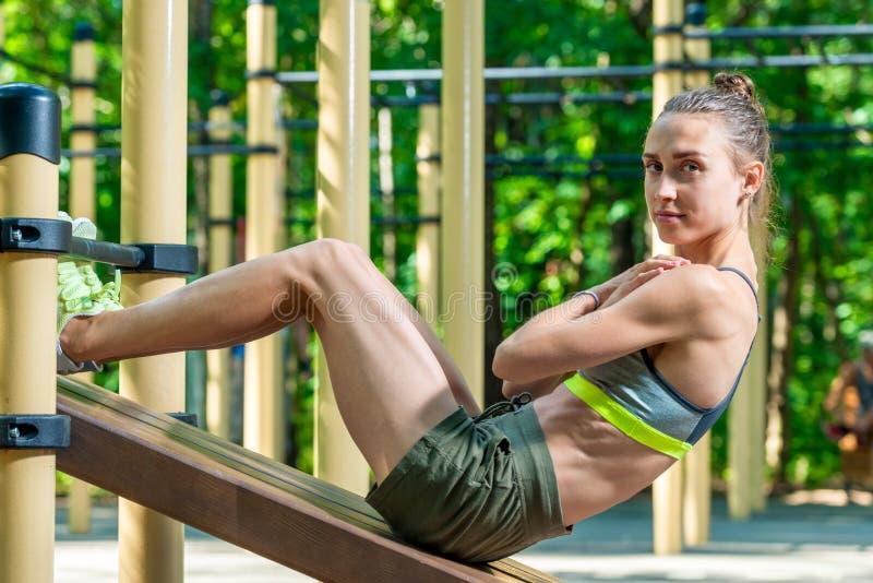 schöne Sportlerin rüttelt ihre Presse auf dem Spielplatz im Park auf einem Sommer lizenzfreies stockbild
