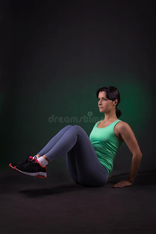 Schöne sportliche Frau, die Übung auf einem dunklen Hintergrund mit grüner Hintergrundbeleuchtung tut lizenzfreies stockfoto